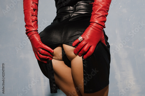 Tuinposter Ezel Sexy woman in a dress with a cut back stand in red gloves holding herself in the ass