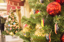Christmas Tree Background And Christmas Decorations In The Mall. Colorful Balls And Sneakers Toys On Green Fir. New Year Theme