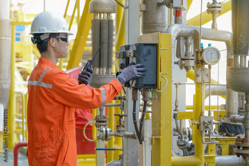 Fotografiet  Production operator operating centrifugal oil pump by using local mode to start and another hand using walkie talkie to talk with central control room, offshore oil and gas industry business