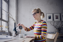 Woman Pouring Coffee In Mug At Desk
