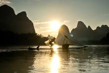 Cormorant Fisherman On His Bamboo Raft At Sunset