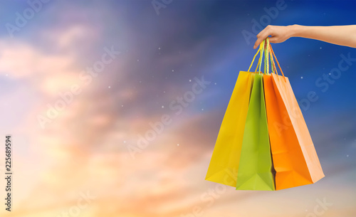 Photo Stands sale, consumerism and concept - close up of male hand holding shopping bags over sky background
