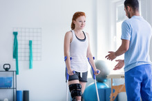 Woman With Crutches During Rehabilitation With Helpful Physiotherapist