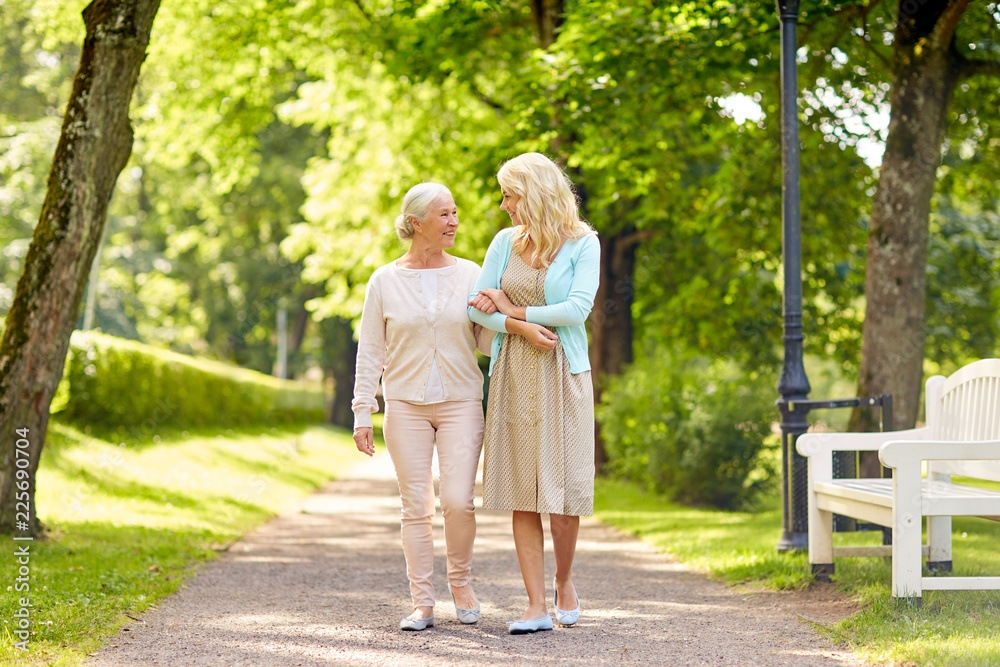 Fototapeta family, generation and people concept - happy smiling young daughter with senior mother walking at summer park