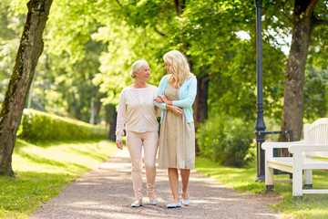 family, generation and people concept - happy smiling young daughter with senior mother walking at summer park