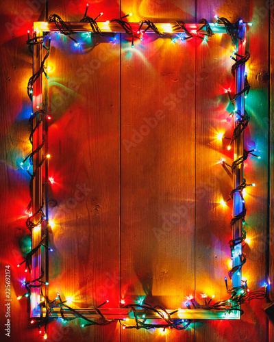 Christmas lights frame on wooden background