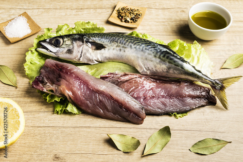 Foto op Aluminium Vis Mackerel fresh fish on lettuce leaves next to bay leaves, a few pieces of lemon, a bowl of oil and some spices on a wooden table