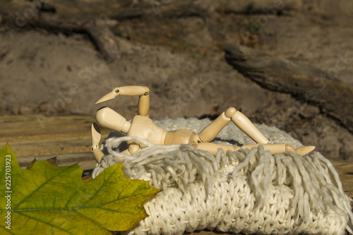 Fotografie, Obraz  Dummy for drawing in relaxing pose lays on the warm scarf near fallen leaves
