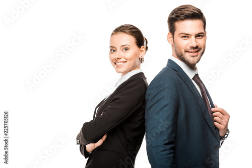 Fototapeta happy young business partners leaning back to back and looking at camera isolated on white obraz