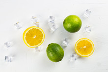 Fresh Lime And Lemon On White Texture Surface With Crystal Ice Cubes. Close Up.
