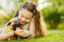 Little Girl Kid Feeding Pug Dog On Summer Day