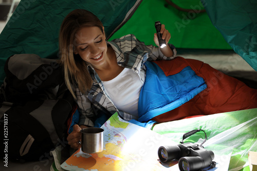 Obraz Young woman in sleeping bag with map and flashlight inside of tent - fototapety do salonu