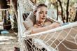 Calm weekend. Pleasant pretty woman spending weekend in the park lying in hammock