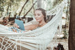 Feeling excited. Attractive pleasant woman watching interesting film on a laptop lying in a hammock