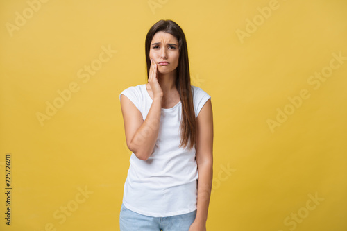 Fotografia  young woman has a toothache, studio photo isolated on a yellow background