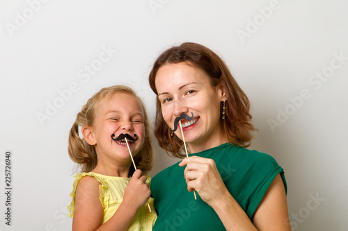 Photo  Mother and her child daughter girl with a paper accessories.