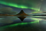 The Northern Light at the mountain Kirkjufell Iceland. Amazing landscape with green bands of Aurora Borealis. Snaefellnes, Iceland
