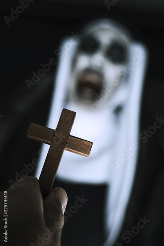 Photo frightening evil nun screaming in front of a cross.