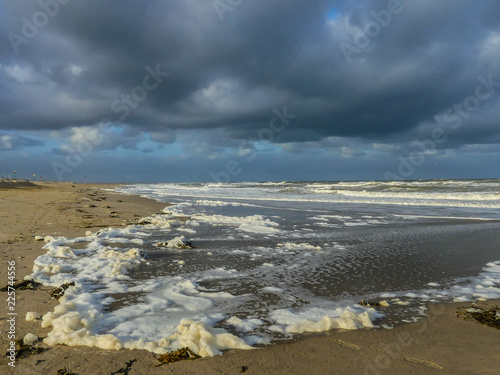 Foto op Canvas Kust Kijkduin beach, The Hague, the Netherlands - October 3 2018: foam washing ashore during north sea storm on dutch coast