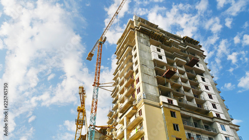 Spoed Foto op Canvas Stad gebouw Construction site background. Skyscraper construction. Two cranes near building.