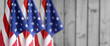 Three American flags in front of blurred wood background