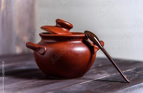 Obraz na płótnie Clay pot with a spoon on a wooden table