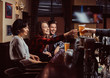 Young multiracial friends in bar. barman giving glass of beer to customer in pub.
