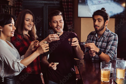 Foto  Group of happy multiracial friends making a toast with vodka while standing at bar or pub