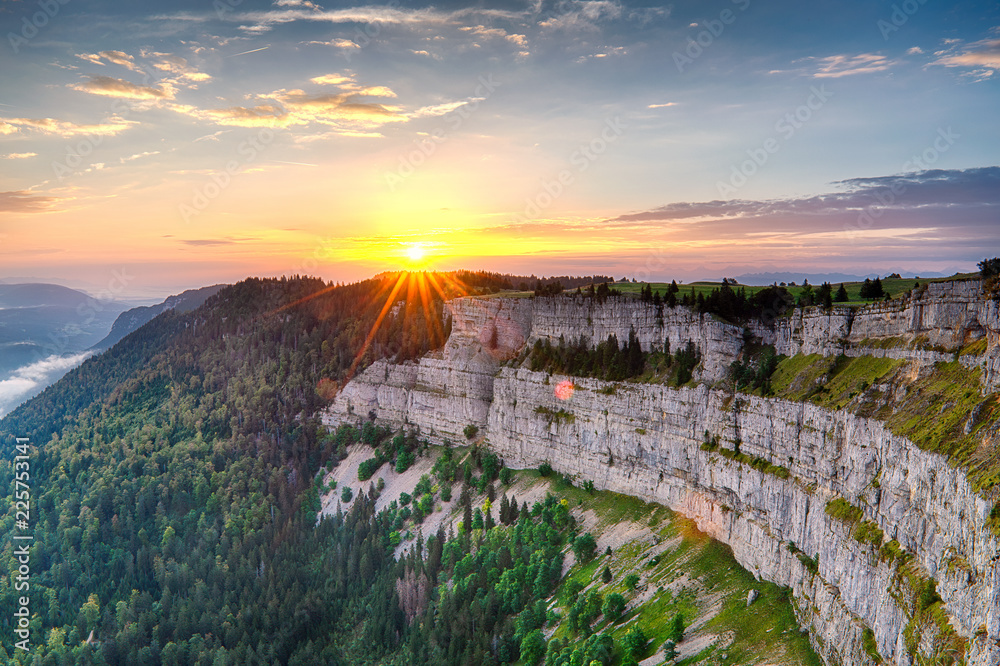 Fototapety, obrazy: Vivid sunset with sunstar over cliff Creux du Van Neuchatel in warm light with sceenic view on valley and green forest