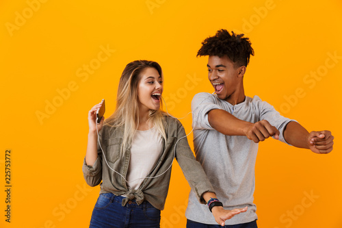 Papiers peints Akt Happy young loving couple dancing isolated over yellow background listening music by earphones.