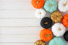 Autumn Side Border Of Various Colorful Pumpkins On A White Wood Background. Top View With Copy Space.