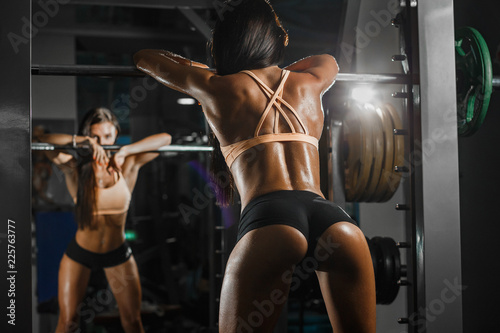 Fotografie, Tablou Attractive sporty woman relaxing with barbell in gym