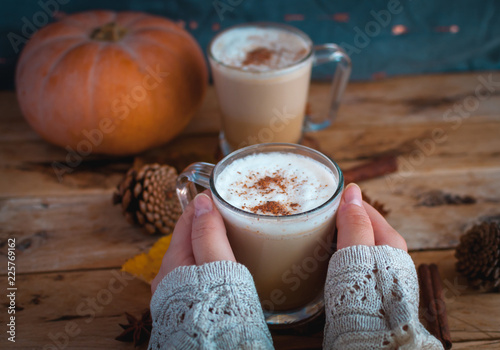 Fotografia Close-up of hand holding pumpkin spice latte in glass cup on wooden background