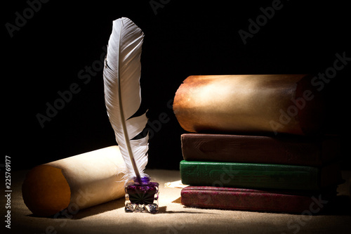 Literature concept. Old inkstand with feather near scrolls and books against black background. Dramatic light