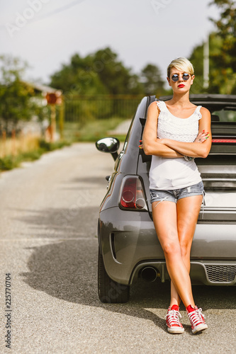 Young pretty fashionable woman posing on a car. Concept young lifestyle.