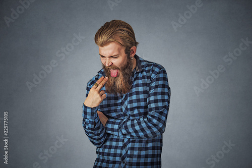 Fotografie, Tablou  disgusted man with finger in mouth displeased wants to throw up