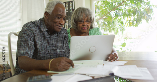 Foto Mature African couple reading on their laptop computer