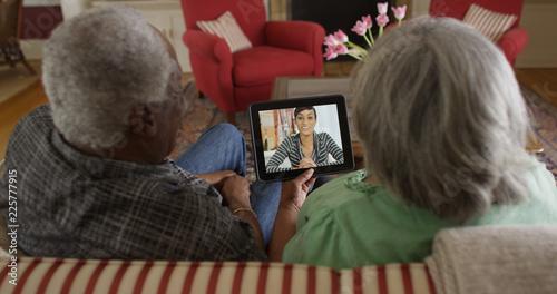 Happy senior black couple video chatting with granddaughter Fototapet
