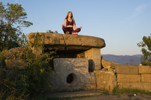 Girl Meditating On Ancient Stone Dolmen
