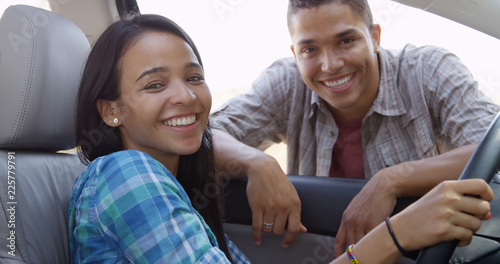 Foto  Happy young couple smiling together in car and looking at camera