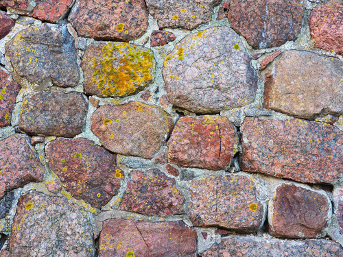 Old red granite stone texture. Ancient masonry background, close-up. Wall of the medieval city, castle retro background. Xanthoria parietina
