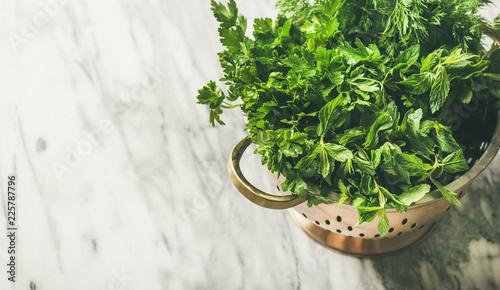 Fotobehang Aromatische Bunch of fresh green garden herbs in brass colander over marble kitchen table background, top view, copy space, horizontal composition