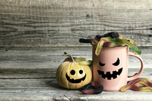 Halloween Holiday Mug With Candy Worms And Pumpkin With Funny Faces On The Old Wooden Table.
