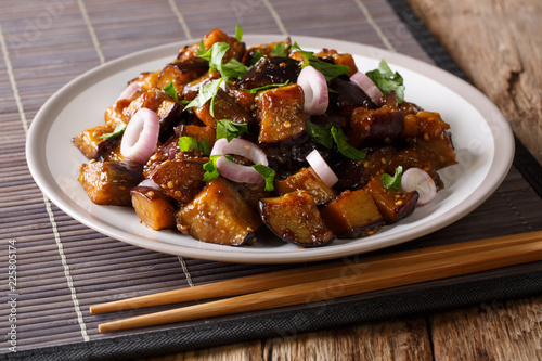 stir fried Szechuan eggplant  in spicy soy sauce with ginger, garlic, pepper, closeup on a plate on the table. Horizontal