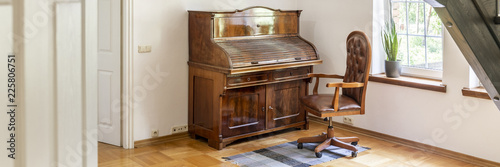 A wooden antique secretary and a matching desk chair on a parquet in an office interior of a luxury estate Canvas-taulu