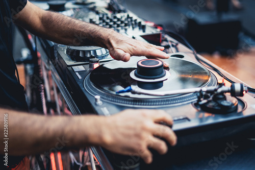 dj scratching a vinyl disc on a professional turntable, focus on the left hand scratching Canvas Print