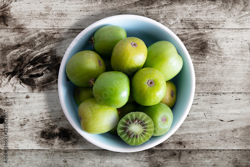 hardy kiwi fruits or kiwi berry actinidia arguta in ceramic bowl on wooden kitch Wallpaper Mural