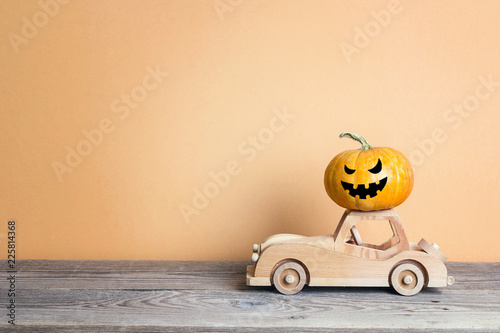 Wooden toy car with funny evil pumpkin on the roof on orange background. Space for text.