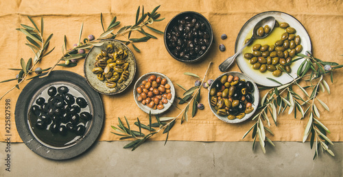Flat-lay of various kinds of Mediterranean pickled olives in plates and bowls and olive tree branches on yellow linen cloth, top view, copy space, wide composition. Mediterranean meze appetizer