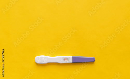 Fotografiet  Pregnancy test on a yellow background. Close-up.